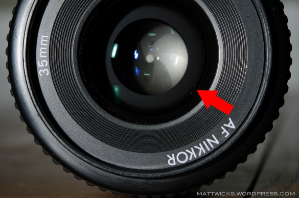"The two white dots on the front element just inside the ""AF Nikkor"" text?  Scratches.  The other crap?  Dust.  And probably more scratches.  Maybe this veteran is due for replacement with something like a Sigma 35mm f/1.4 DG HSM."