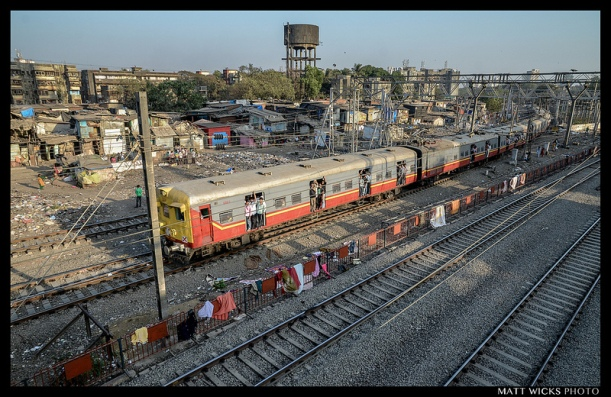 A commuter train passes through the world's largest slum.  Mumbai, Maharashtra, India.